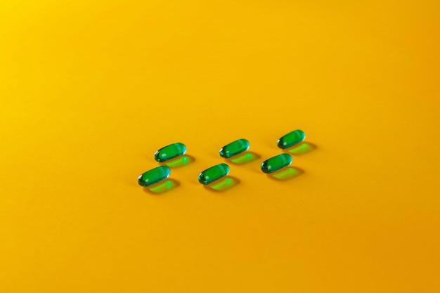 Sei pillole trasparenti verdi su un giallo. salute. uno stile di vita sano . il concetto di farmacologia. il concetto di medicine. il concetto di strumenti medici.
