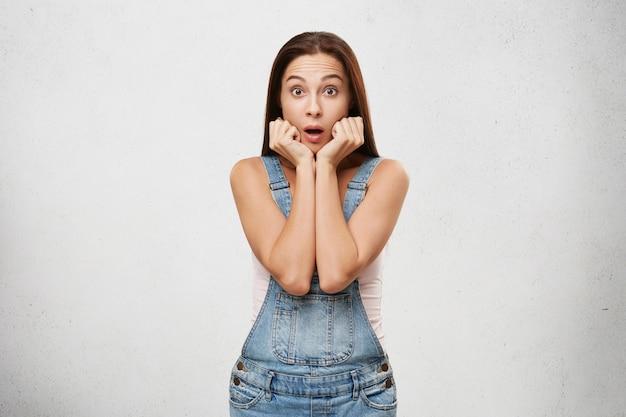 Sei serio? l'errore di programma sorpreso ha osservato il giovane cliente o studente femminile castana attraente che si tiene per mano al suo fronte che guarda nell'incredulità completa dopo la ricezione delle notizie scioccanti sorprendenti. linguaggio del corpo