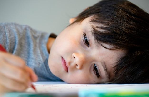 Selctive focus ragazzo bambino solitario sdraiato a testa in giù sul tavolo con la faccia triste, ritratto emotivo di cinque anni vecchio ragazzo annoiato con compiti a scuola, bambino viziato