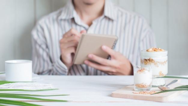 Seleziona messa a fuoco pasto sano fatto di muesli in vetro con sfocatura scrittura asiatica maschio sul notebook
