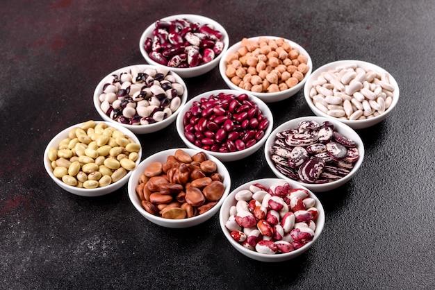 Selezione di alimenti biologici a base di legumi in piatti di porcellana bianca.