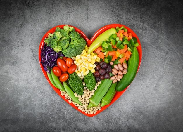 Selezione di alimenti sani mangiar pulito per la vita del cuore colesterolo dieta salute insalata fresca frutta e verdure verdi miste vari fagioli noci grano sul piatto cuore rosso per cibo sano cuoco vegano