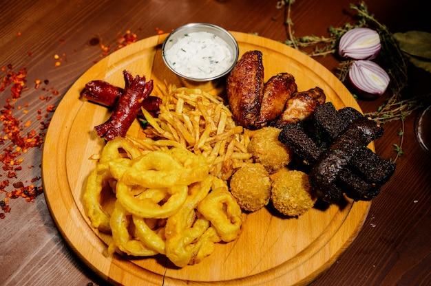 Selezione di birra e snack. patatine, pesce, salsicce di birra sul tavolo