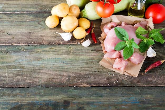Selezione di carne cruda di pollo con verdure al bordo di legno. proteine magre.