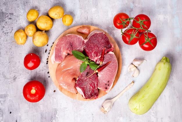 Selezione di diverse carni crude con verdure al bordo di legno. proteine magre.
