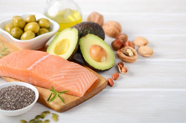 Selezione di grassi insaturi sani, omega 3 - pesce, avocado, olive, noci e semi.