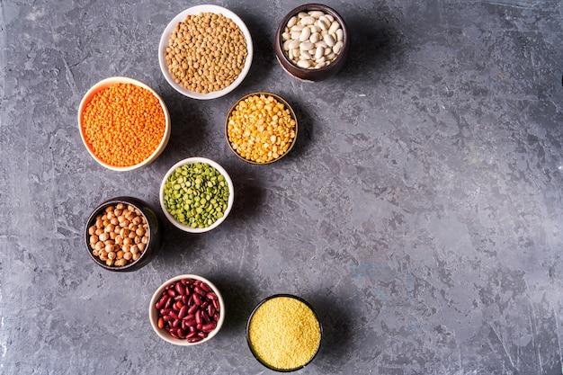 Selezione di legumi. fagioli, lenticchie, ceci, piselli in ciotole su sfondo grigio cemento.