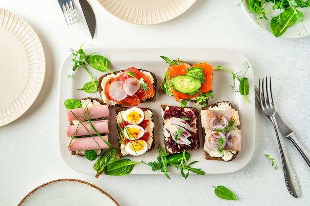 Selezione di smorrebrod danese sandwich aperti su un piatto, foglie di insalata, piatti, posate sul tavolo bianco