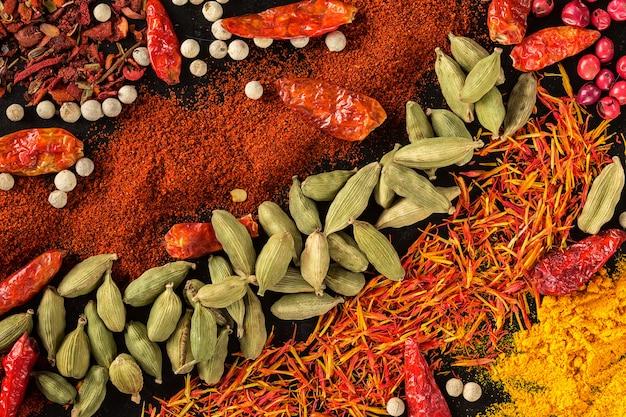 Selezione di spezie ed erbe aromatiche su fondo nero