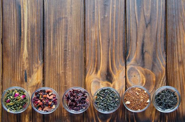 Selezione di tè assortiti in piccole ciotole trasparenti su legno naturale