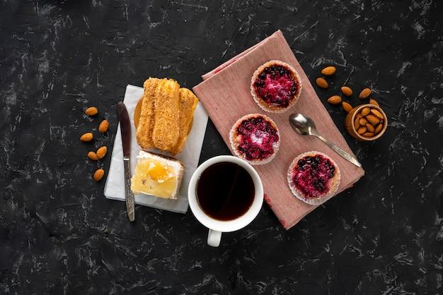 Selezione di torte dolci, cupcake e cheesecake, caffè caldo sul tavolo, noci di mandorle in una ciotola