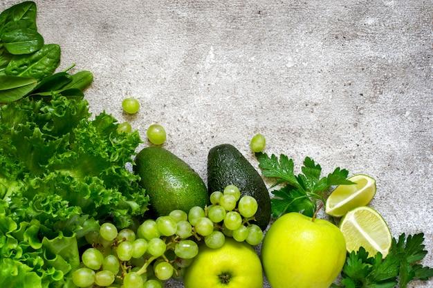 Selezione di verdure verdi e frutta su un dorso di cemento grigio