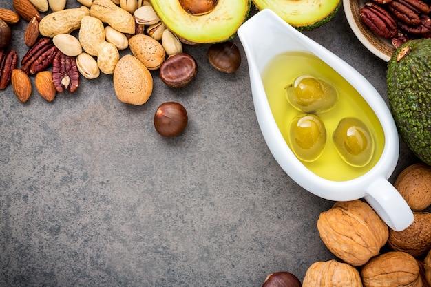 Selezione fonti alimentari di omega 3 e grassi insaturi su sfondo di pietra scura.