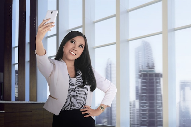 Selfie asiatico della presa della donna di affari