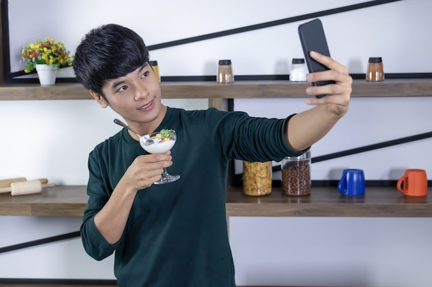 Selfie bello del giovane felicemente nella cucina