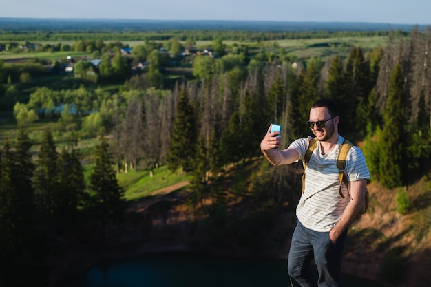 Selfie bello della fucilazione dell'uomo nella natura. escursione. momenti di alpinismo. scatto con splendide vedute di paesaggi forestali. in armonia con la natura. sport e divertimento all'aria aperta