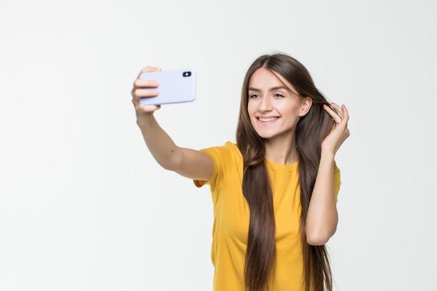 Selfie castana della presa della donna con lo smart phone isolato sulla parete bianca