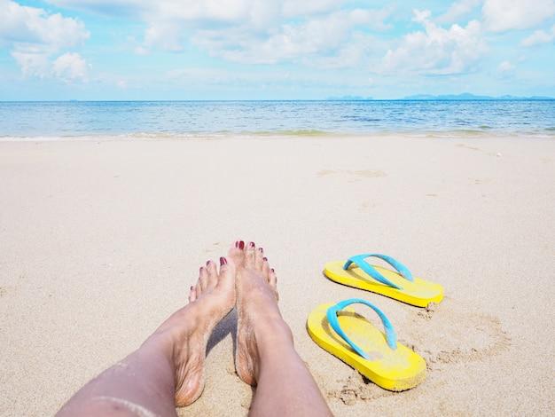 Selfie della donna a piedi nudi e sandali gialli sulla spiaggia.