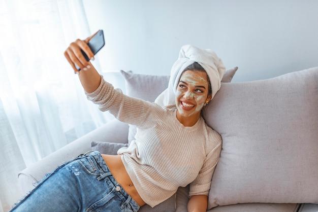 Selfie di bella donna felice dopo la doccia con un asciugamano in testa, con crema sul viso.