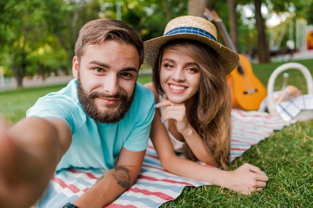Selfie di giovani coppie sul picnic nel parco con la chitarra e il canestro di frutta