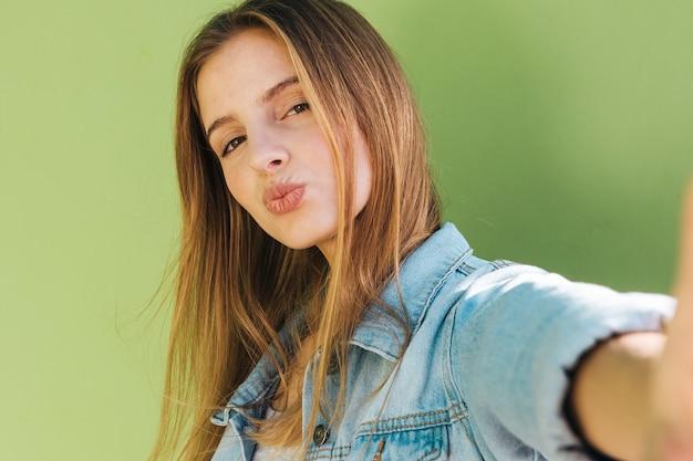Selfie di presa bianco sporgente le labbra della giovane donna bionda sul telefono cellulare