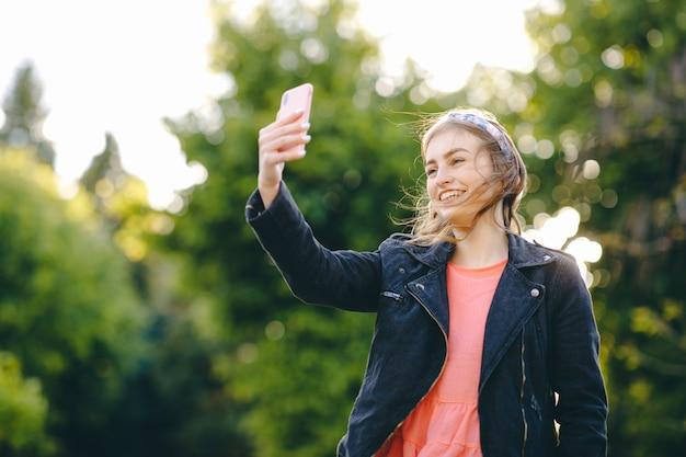 Selfie di presa femminile giovane felice. la ragazza che comunica con l'amico online fa la videochiamata che parla il colloquio di lavoro a distanza del vlog di stile di vita