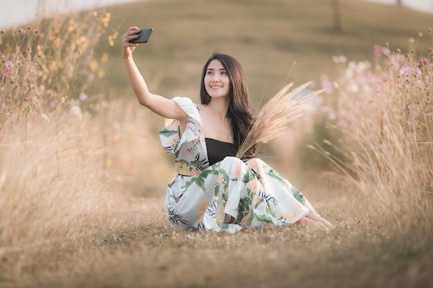 Selfie di seduta della bella ragazza asiatica delle donne sullo smartphone nell'annata di stile dell'immagine del fiore del parco