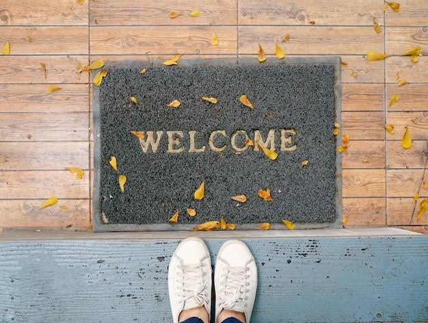 Selfie di vista superiore dei piedi in scarpe da tennis bianche sul pavimento con tappetino di benvenuto