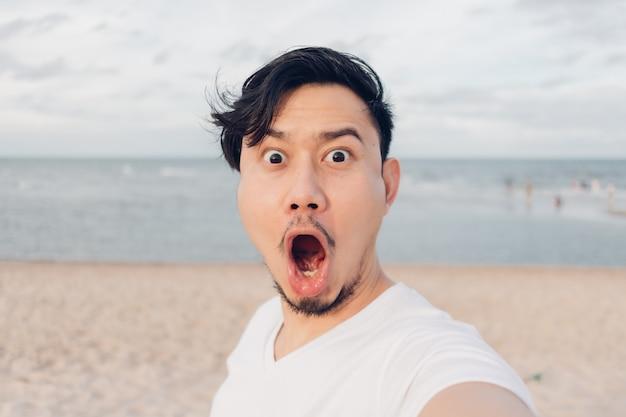 Selfie felice se stesso mentre si cammina sulla spiaggia.