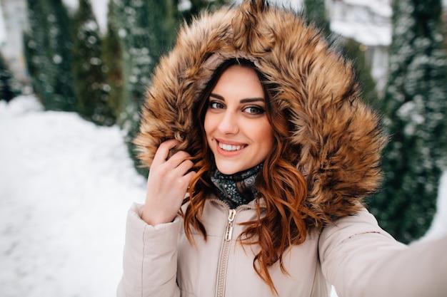 Selfie invernale la bella ragazza in cappuccio della pelliccia prende il selfie nel giorno di inverno nevoso