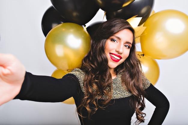 Selfie ritratto divertente incredibile ragazza in abito elegante moda tra palloncini oro e neri su uno spazio bianco