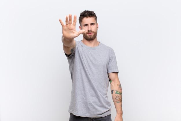 Sembra serio, severo, scontento e arrabbiato mostrando il palmo aperto facendo fermare il gesto