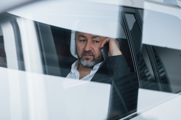 Sembra stanco. riflessione sulla finestra. avere una chiamata di lavoro mentre era seduto sul retro di un'auto di lusso moderna