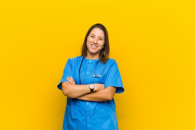 Sembrando un felice, orgoglioso e soddisfatto raggiungendo sorridente con le braccia incrociate isolato contro il giallo