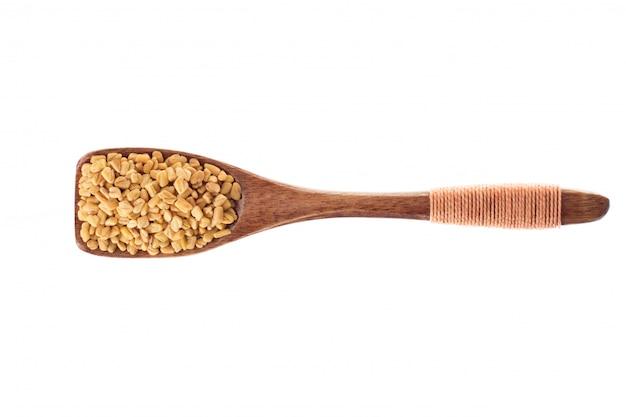 Seme del fieno greco della spezia in cucchiaio di legno isolato su un fondo bianco, vista superiore