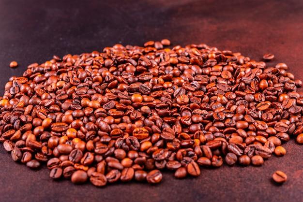 Semi di caffè fragrante su uno sfondo di cemento scuro. può essere usato come sfondo