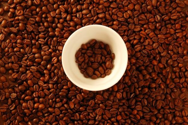 Semi di caffè marrone dorato, intorno alla tazza bianca