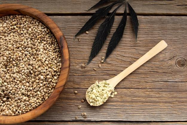 Semi di canapa non sbucciati in una tazza di legno su una tavola di legno. nelle vicinanze si trova un cucchiaio di legno con una manciata di semi pelati e una foglia di pianta di canapa. cibo super. fonte di vitamine