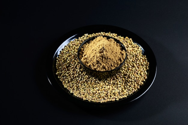 Semi di coriandolo e polvere su fondo nero