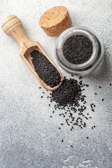 Semi di cumino neri su un cucchiaio di legno e in un barattolo di vetro su gray