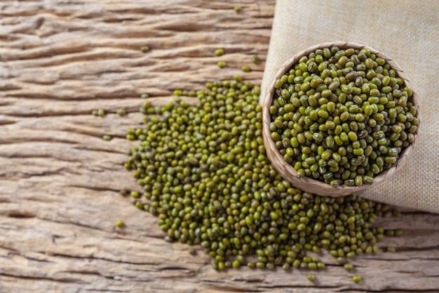Semi di fagiolo verde su un fondo di legno in cucina