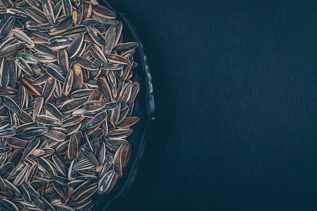 Semi di girasole neri in una zolla su una priorità bassa nera. vista dall'alto. spazio per il testo