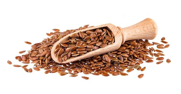 Semi di lino isolati, primo piano dei semi di lino in mestolo di legno