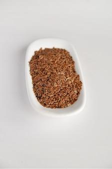 Semi di lino su un piatto bianco sul tavolo
