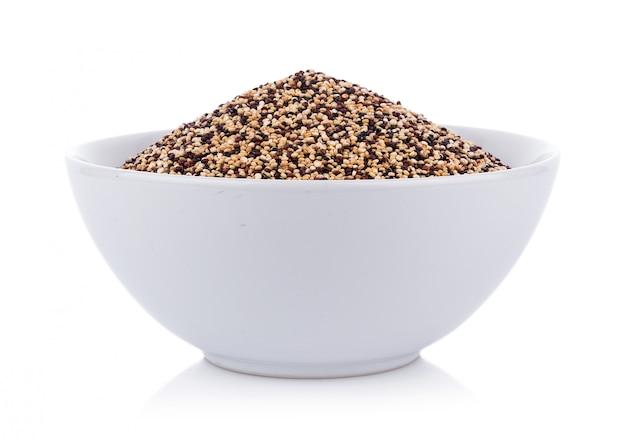 Semi di quinoa reali in una ciotola isolata su bianco