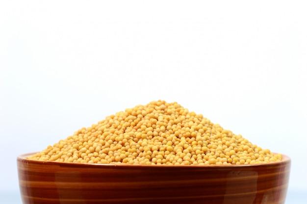 Semi di senape gialli in ciotola isolata