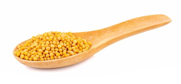 Semi di senape in cucchiaio isolato