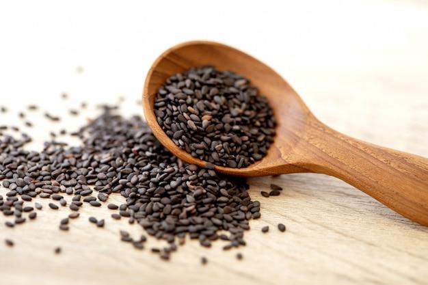 Semi di sesamo neri biologici in un cucchiaio di legno, un alimento sano per la riduzione della pressione arteriosa sistolica e diastolica