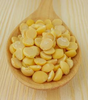 Semi di soia in un cucchiaio di legno