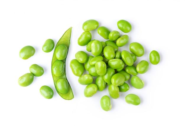 Semi di soia verde sulla parete bianca.